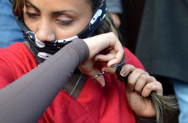An Egyptian women cutting her hair in protest at the new constitution