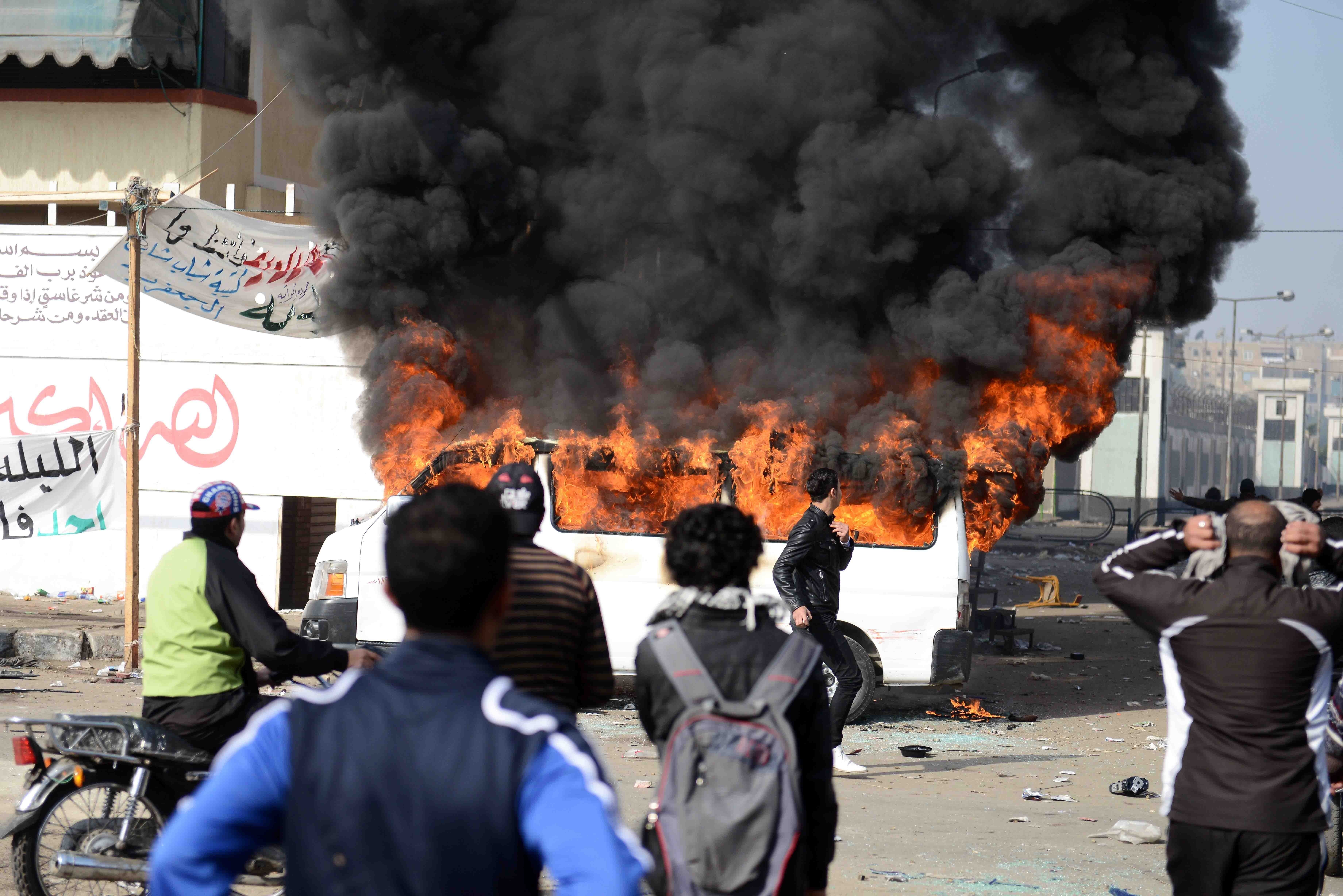 Smoke billows from a burning minibus belonging to a satellite channel after it was set on fire by Egyptian protesters outside the Port Said prison in the Egyptian canal city on Saturday (Photo courtesy of AFP)