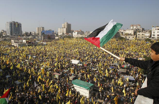 Fatah and Hamas supporters rally in Gaza on January 4, 2012. (AFP Photo)