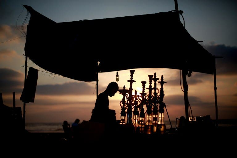 A man readies water pipes as the sun sets over the Gaza Strip during Ramadan. (AFP / Mohammed Abed)