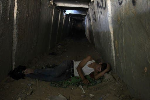 A Palestinian tunnel worker rests at the entrance of a smuggling tunnel dug beneath the Gaza-Egypt border in the southern Gaza Strip on August 27, 2013.(AFP)