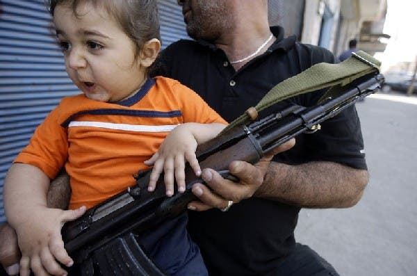 A Sunni Muslim gunman sits with his child on Syria Street during fighting in the Bab al-Tebbaneh neighbourhood of the northern Lebanese city of Tripoli. AFP Photo/Getty Images