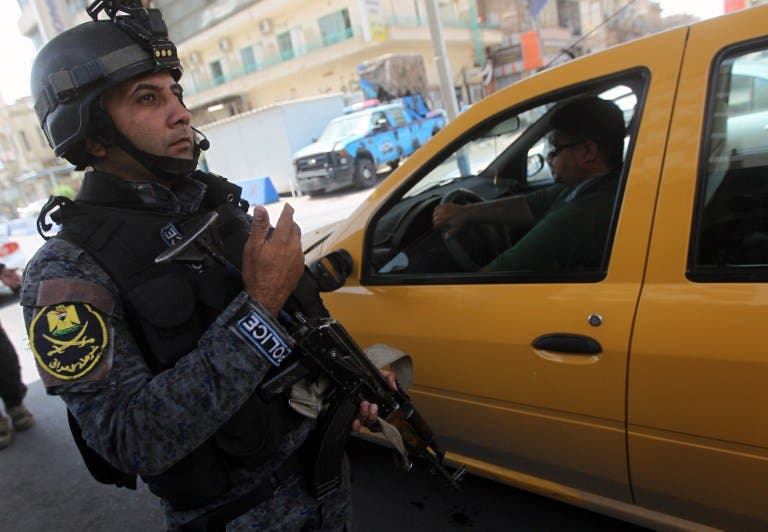 An Iraqi policeman checks vehicles on July 23 after security measurers were increased in Baghdad. (AFP / AHMAD AL-RUBAYE)