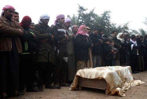 A family gathers to pray over the body of one of their relatives who was killed this weekend in clashes in Fallujah (AFP)