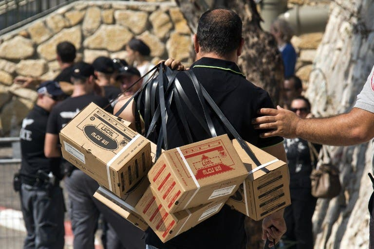 ISRAEL, Haifa : An Israeli man carries gas mask kits as he leaves a distribution center in the Mediterranean coastal city of Haifa, north of Israel, on August 29, 2013. AFP PHOTO / JACK GUEZ