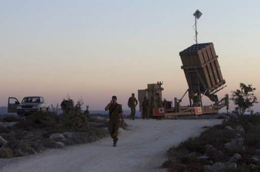 Israeli soldiers stand near an Iron Dome battery, a short-range missile defence system, designed to intercept and destroy incoming short-range rockets and artillery shells, near Jerusalem on Sunday. (AFP)