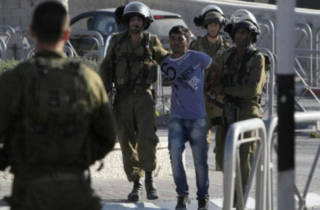 Israeli soldiers arrest a Palestinian youth in the West Bank's Qalandiya refugee camp on August 26, 2013. (AFP)