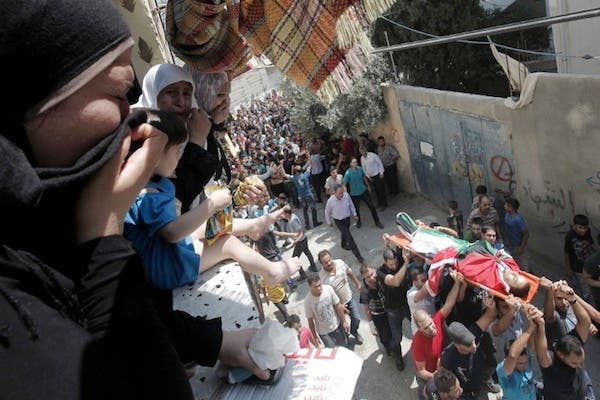 Palestinian mourners cry as other carry the body of Majd Lahluh, who was killed by Israeli soliders, during his funeral at Jenin refugee camp in the West Bank city of Jenin on August 20, 2013. (AFP)