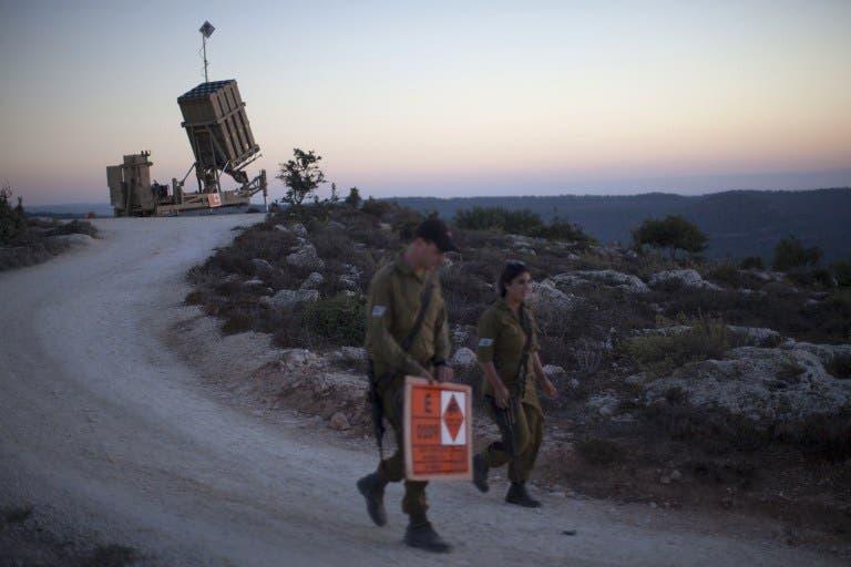 Israeli soldiers walk by an