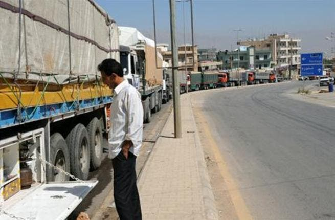 Dozens of trucks line up at the Lebanese-Syrian border in Masnaa.