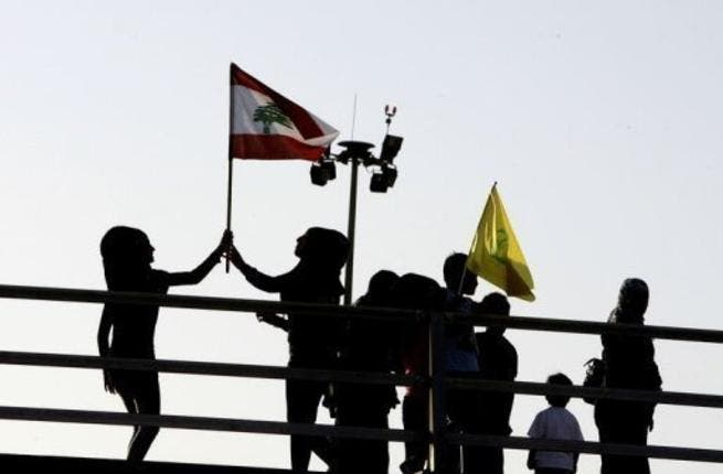 Hezbollah on Monday re-pledged its support to the Syrian regime and vowed to attack Israel. Lebanese children fly the national Lebanese flag (L) and the Hezbollah flag. (AFP/File)