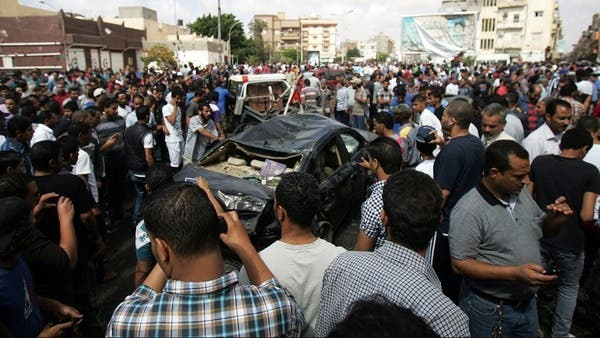 Bystanders and residents gather next to the wreckage of a car at the site of a car bomb that exploded in the parking lot of a Benghazi hospital in Libya on Monday. (AFP Photo)
