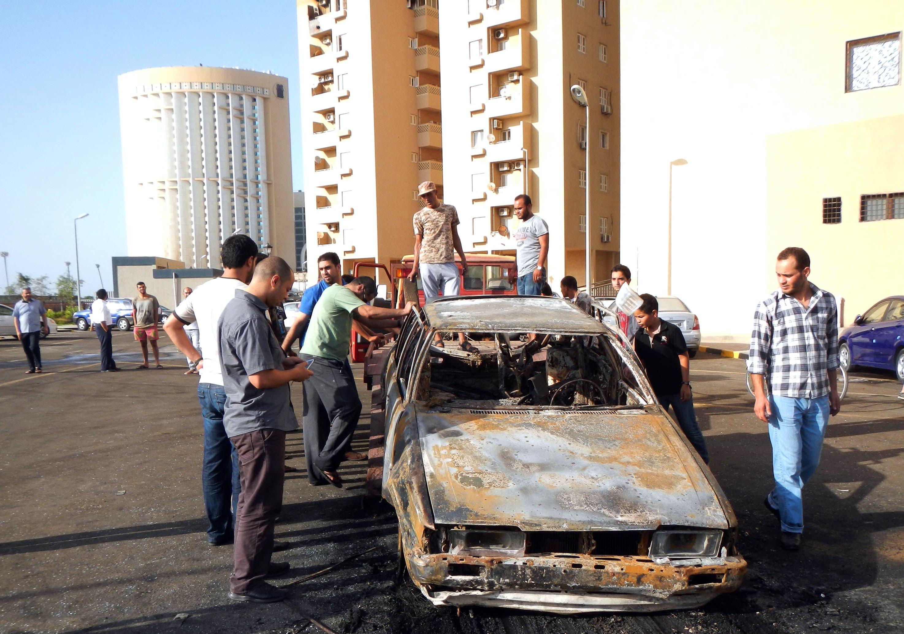Men examine a car destroyed in a blast near embassies in Tripoli (AFP / MAHMUD TURKIA)