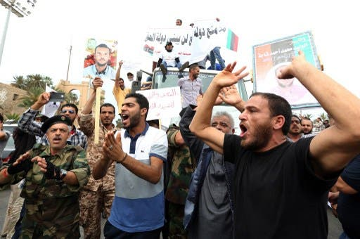 Libyan protesters hold placards and banners during a demonstration in support of the