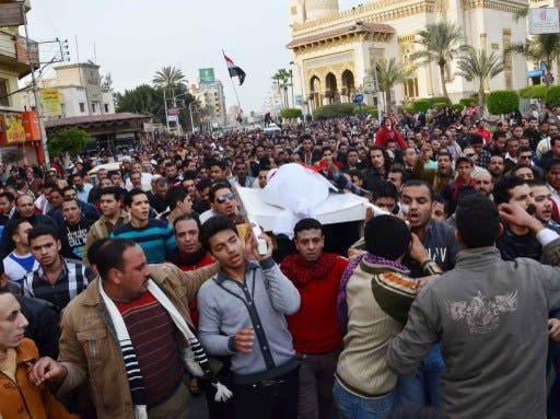 Egyptians carry the body of a person killed in overnight clashes between police and protesters in Egypt's Nile Delta city of Mansura, on Saturday. (Photo: AFP / STR)