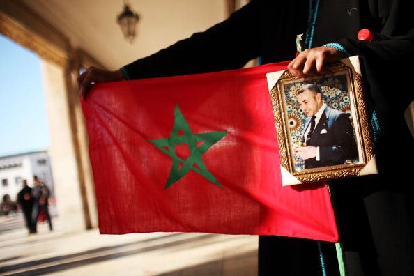 A woman holds a Moroccan flag and a portrait of King Mohammed VI at a protest in 2011. (Source: Spencer Platt / Getty)
