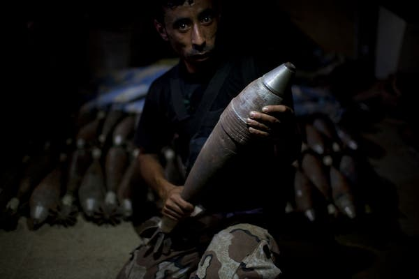 A rebel fighter holds an improvised mortar shell, one of many stacked at a factory in the city of Aleppo, Syria's commercial capital, on July 7, 2013. (Source: AFP/JM LOPEZ)
