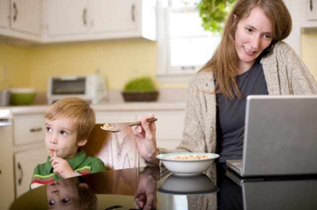 Mothers are often expected to be the best multi-taskers: but here the mother might miss the child's mouth altogether as she juggles work and feeding.