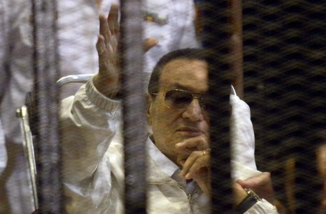 Hosni Mubarak waves from his bed during his retrial which was quickly adjourned (AFP)
