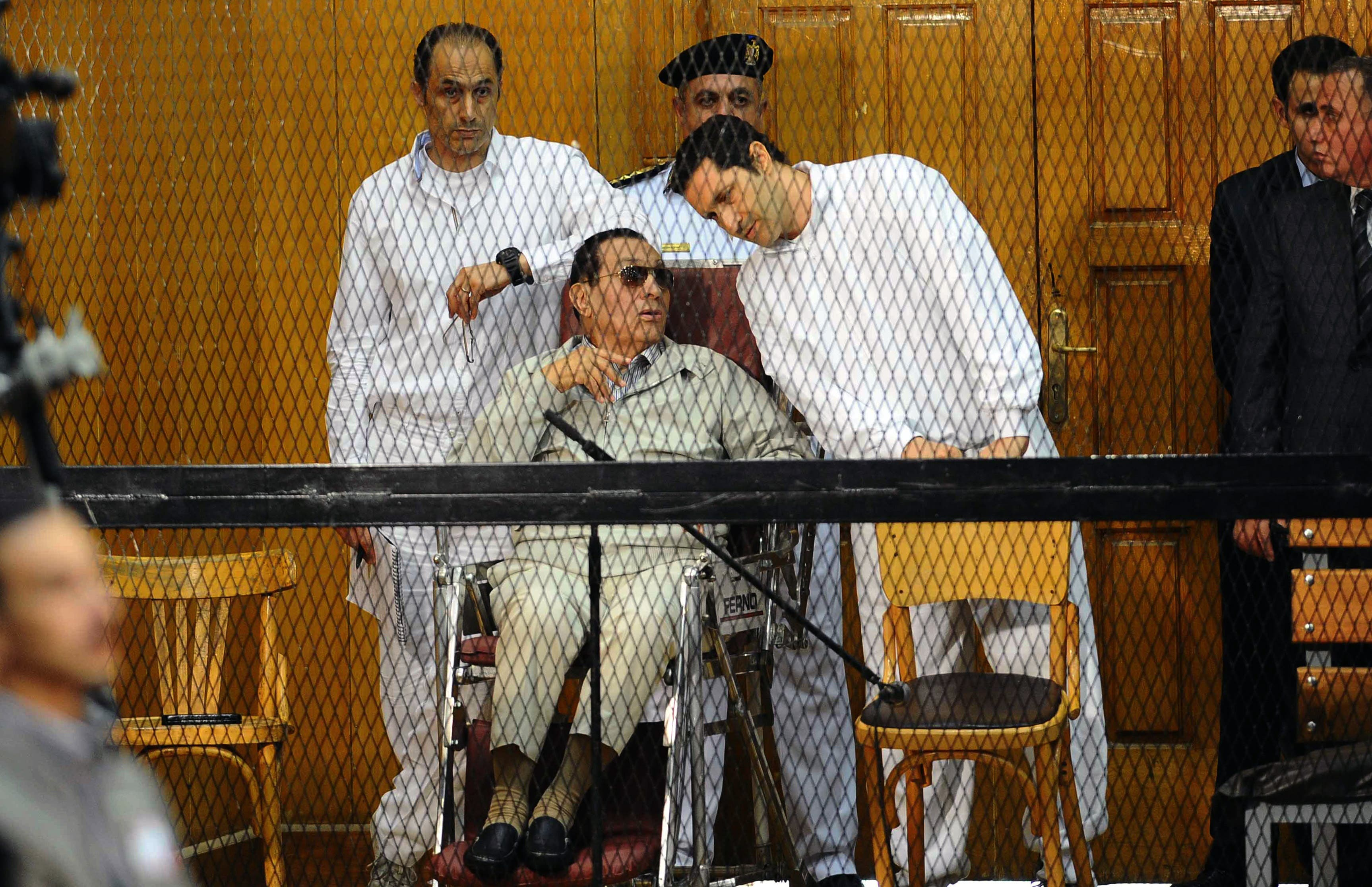 Egyptian toppled president Hosni Mubarak and his two sons Alaa (R) and Gamal stand behind bars during their trial at the Police Academy on September 14, 2013 in Cairo (AFP)