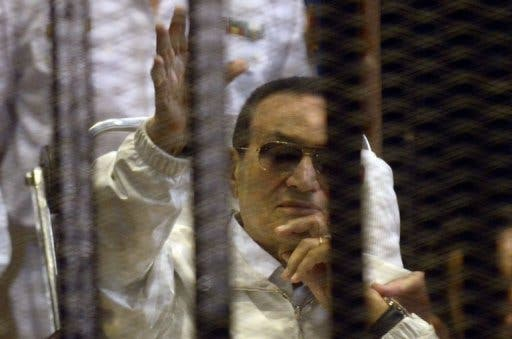 Hosni Mubarak waves from his hospital bed in court (AFP)