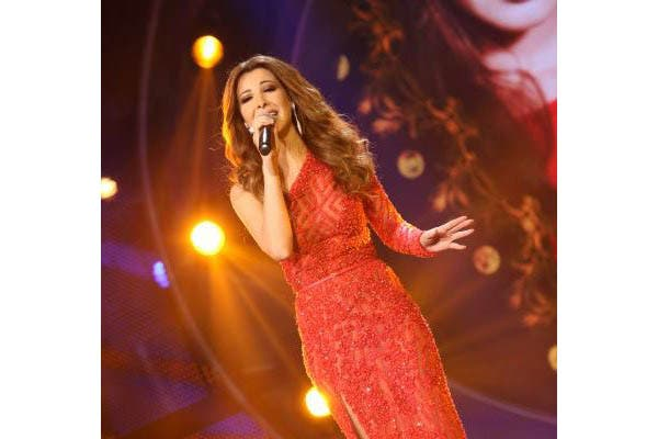 Nancy Ajram is the lady in red, performing as guest star on Arab Idol.