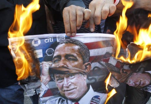 A protester holds a poster burning on which is depicted former US president George W. Bush taking off a mask of current President Barack Obama during a demonstration of in Beirut. (AFP)