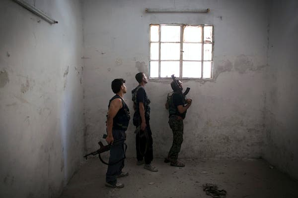 Rebel fighters look at the pro-government forces' positions through a window as they hold a position in an empty room in the Salaheddine district of the northern Syrian city of Aleppo, on July 9, 2013. (Source: AFP/JM LOPEZ)