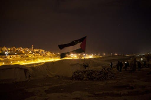 A Palestinian flag flutters at a protest camp in the controversial West Bank area known as E1 located east of Jerusalem and near the Jewish settlement of Maaleh Adumim early on Sunday. Hundreds of Israeli police dismantled the protest camp on the outskirts of Jerusalem overnight, activists and police said. (Photo: AFP / Ahmad Gharabli).