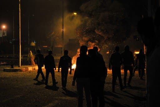 Egyptian protesters stand near burning tyres outside the main security headquarters in the canal city of Port Said early on Tuesday. (Photo: AFP/STR)