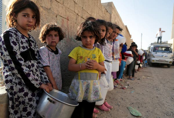 """Syrian children wait in line to collect a free """"Iftar"""" meal in the northern city of Raqqa during the Muslim holy month of Ramadan on July 14, 2013 (Source: AFP/MEZAR MATAR)"""