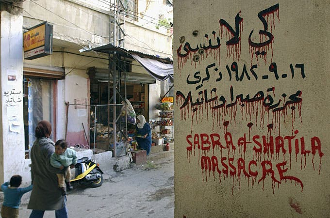 A Palestinian woman passes by a sign marking the 1982 Sabra and Shatila massacre in Beirut, Lebanon [GALLO/GETTY]