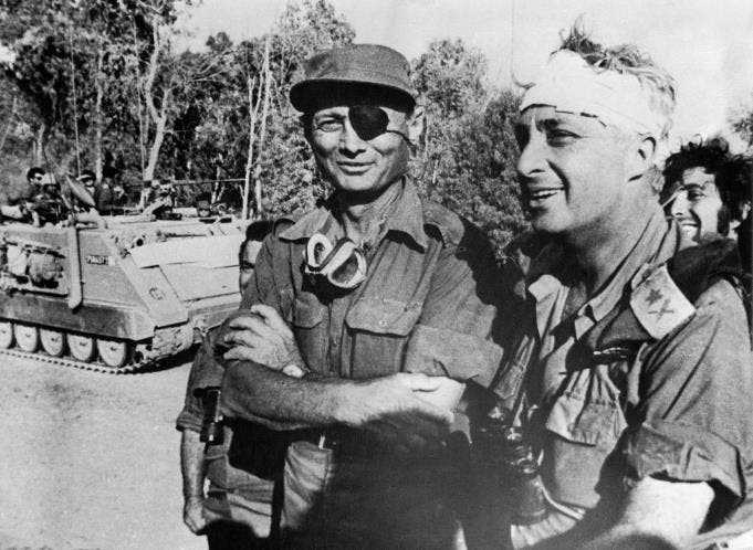 A file picture taken in October 1973 and provided by the Israeli Army shows Ariel Sharon with Moshe Dayan on the western side of the Suez Canal during the Yom Kippor war. [AFP]