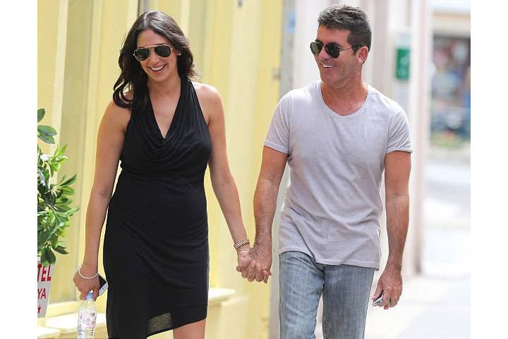 Hand in hand: Simon Cowell and girlfriend Lauren Silverman smile away as they stroll along on a lunch date. (Image: Facebook)