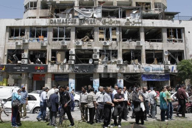 People stand on a street lined with a damaged building and destroyed cars after a blast at Marjeh Square in Damascus in April. Image courtesy of nydailynews.com