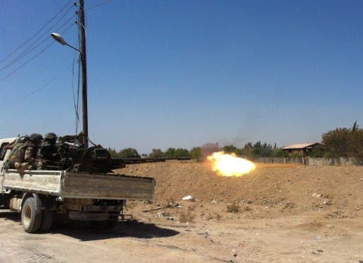 Syrian troops fire a heavy machine gun mounted on a pick-up truck in the Eastern Ghouta area on the northeastern outskirts of Damascus on August 30, 2013. (AFP)