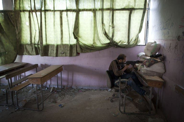 A rebel fighter takes aim inside a destroyed school in Aleppo, on July 14. 2013. (source: AFP / JM LOPEZ)
