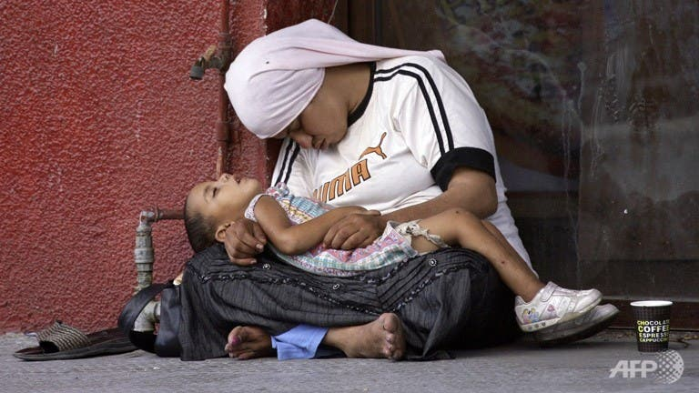 A Syrian refugee holds her child as they doze off at a street in the southern Lebanese city of Sidon. (AFP)
