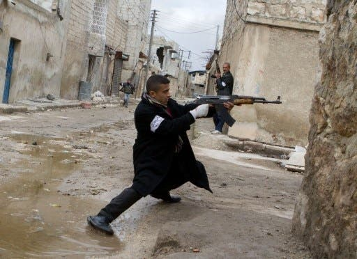 A Syrian rebel aims his weapon during clashes with government forces in the streets near Aleppo international airport in northern Syria on Monday (Photo: AFP/Stephen J. Boitano) - Picture used for illustrative purposes -