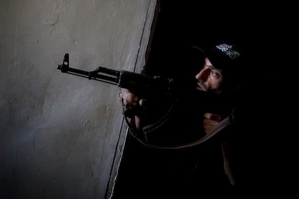 A rebel fighter points his gun towards pro-government forces' positions during clashes in the Salaheddine district of the northern Syrian city of Aleppo, on July 9, 2013. (Source: AFP/JM LOPEZ)