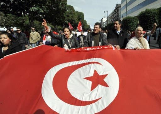 Tunisian people wave a giant national flag during a demonstration to mark the 40th day of mourning after the death of anti-Islamist opposition leader Chokri Belaid (featured on poster) on Saturday on the Habib Bourguiba Avenue in Tunis. (AFP / Fethi Belaid)