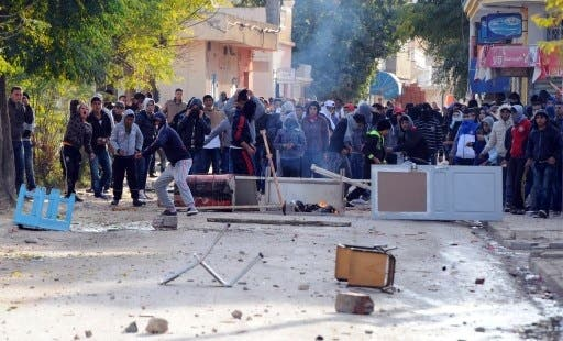 Tunisian protestors hurled stones at security officials late last week, calling for the ruling Islamist party Ennahda's resignation (Fethi Balaid/AFP)