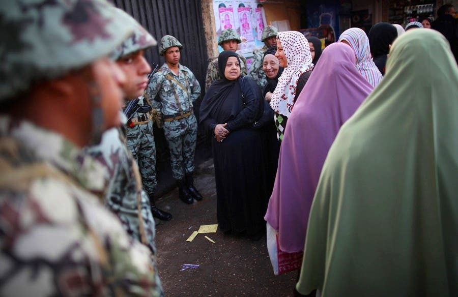 Women standing near The Citadel wait in line to vote watched by soldiers.