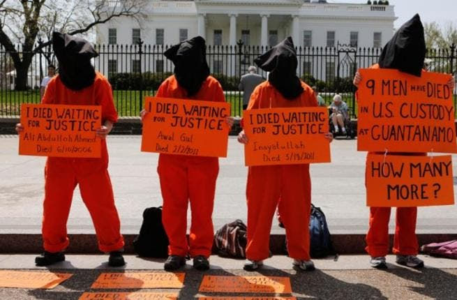 Black hooded human rights activists hold banners demanding the closing of Guantanamo during a protest, part of the Nationwide for Guantanamo Day of Action, outside the White House in Washington DC in April. Photo courtesy of The Week