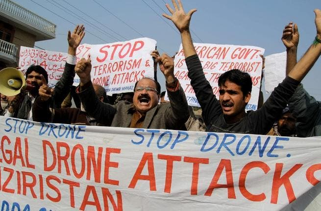 Activists from the Muttahida Shehri Mahaz shout slogans as they protest against a US drone attack in Multan on December 26, 2103. [AFP]