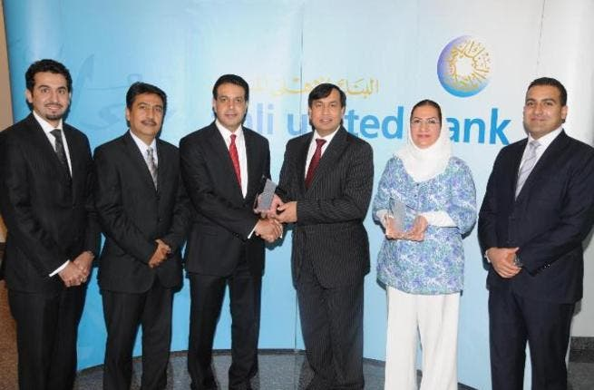 Shafqat Anwar, AUB's Deputy Group CEO, Operations & Technology, receiving the award from Ali Moosa, J.P. Morgan's Managing Director, MENA region