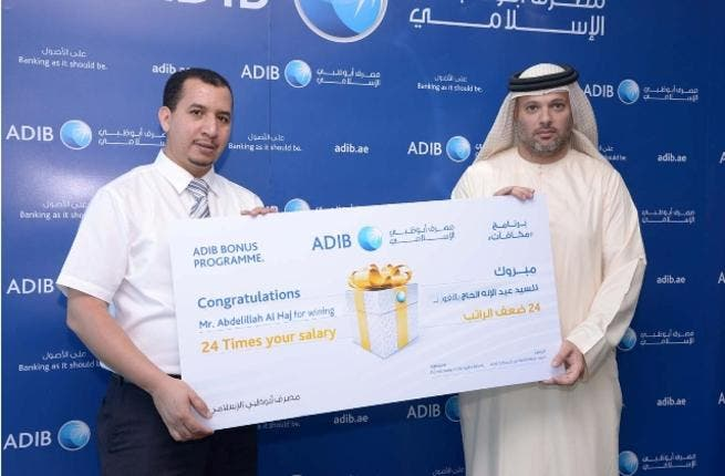 Abdulillah Al Haj receiving the award from Ali Al Bustani, ADIB's Head of Liabilities