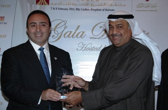Abdul Rahman Mohammed Al Baker, Executive Director of Financial Institutions Supervision at the Central Bank of Bahrain, presenting the award to Walid Sidani, CEO of ADNIC