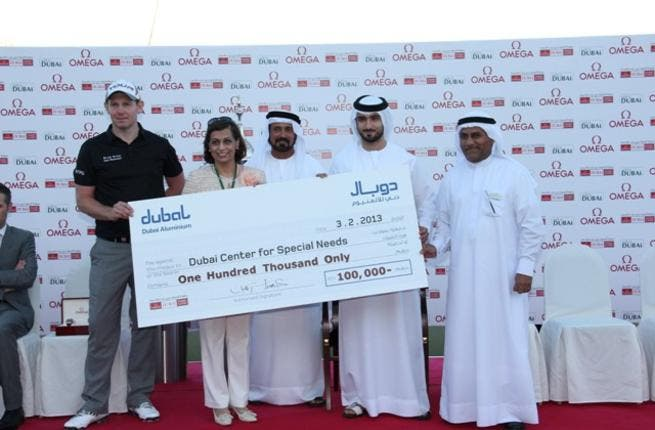 DDC champion Stephen Gallacher with Dr. Maushid from Dubai Center for Special Needs receiving the cheque from Mohamed Yahya