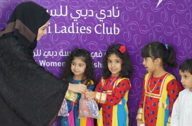 Eman Al Mansoori, Events Manager at Dubai Ladies Club gives children Hag Al Leilah goody bags